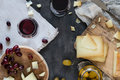 Cheese platter of chopped Spanish hard cheese manchego and sliced Italian pecorino toscano on wooden boards, with green olives Royalty Free Stock Photo