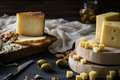 Cheese platter of chopped Swedish hard cheese, sliced Spanishmanchego and Italian pecorino toscano on wooden boards, with olives Royalty Free Stock Photo