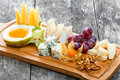 Cheese platter garnished with pear, honey, walnuts, grapes, carambola, physalis on cutting board on wooden background Royalty Free Stock Photo