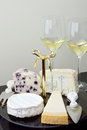 Cheese platter and glasses of wine with camembert parmigiano gorgonzola white stilton with blueberries pointed fork spade shaped Royalty Free Stock Photo