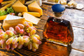 Cheese platter, grapes and a brandy decanter Royalty Free Stock Photo