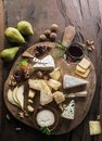 Cheese platter with organic cheeses, fruits, nuts and wine on wooden background. Top view. Tasty cheese starter