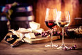 Cheese platter with wine in front of fire Royalty Free Stock Photo