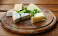 Cheese rustic setting various slices of on a traditional round wooden plate Royalty Free Stock Photography