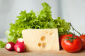 Cheese and vegetables for salad on wooden board in the kitchen Royalty Free Stock Image