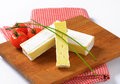 Cheese with white rind sliced soft on wooden cutting board close up Stock Photo