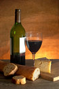 Cheese and wine glass of red with a sliced loaf of freshly made french bread Royalty Free Stock Photos
