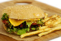 Cheeseburger on the board with french fries lettuce tomato and sauce a wooden chopping and Royalty Free Stock Photography