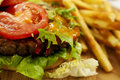 Cheeseburger on the board with french fries lettuce tomato and sauce a wooden chopping and Royalty Free Stock Images