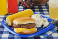 Cheeseburger with corn on the cob a and potato salad a picnic table Stock Image