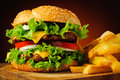 Cheeseburger and french fries closeup of traditional or hamburger Royalty Free Stock Photos