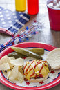 Cheeseburger at a patriotic themed cookout with ketchup and mustard bbq it is served with potato chips pickles and ice tea Royalty Free Stock Photo