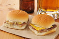 Cheeseburger sliders and beer mini cheese burger with diced onions on a rustic wooden bar counter Royalty Free Stock Photo