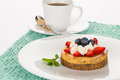 Cheesecake and cup of tea with strawberry blueberry mint cream on white plate with Royalty Free Stock Photos