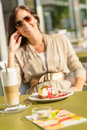 Cheesecake and latte cafe terrace woman sitting Royalty Free Stock Image