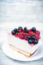 Cheesecake with raspberries red and black currants on a white wood background toning selective focus on berries Stock Photography