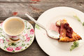 Cheesecake served with fresh turkish coffee topped a berry compote a cup of on an old rustic wooden table for a relaxing Stock Image