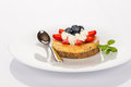 Cheesecake strawberry and blueberry with mint cream on white plate Stock Images