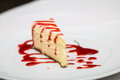 Cheesecake on White Plate with Strawberry Sauce Royalty Free Stock Photo