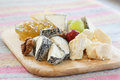 Cheeses delicatessen on a wooden platter Royalty Free Stock Photo