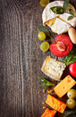 Cheeses and fruit assortment of delicious on a wooden background with copy space for text Royalty Free Stock Photography