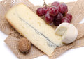 Cheeses and grapes on a burlap isolated white Stock Images