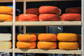 Cheeses on shelf of various colors stacked wooden shelves Royalty Free Stock Photography