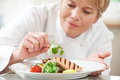 Chef adding garnish to meal in restaurant kitchen dish Royalty Free Stock Photo