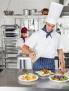 Chef adding oil to dish in kitchen young male on with colleague working background Royalty Free Stock Images