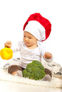 Chef baby with bell pepper holding and broccoli against white background Stock Photos