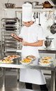 Chef with clipboard checking pasta dishes male in commercial kitchen Royalty Free Stock Images