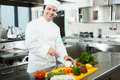 Chef cooking in his kitchen friendly preparing vegetables Royalty Free Stock Images
