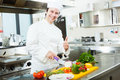 Chef cooking in his kitchen friendly preparing vegetables Royalty Free Stock Image