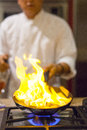 Chef cooking a in the kitchen with flaming gas fire Stock Photos
