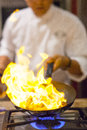 Chef cooking a in the kitchen with flaming gas fire Royalty Free Stock Photography