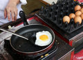 A chef is cooking sunny side up eggs Stock Photo