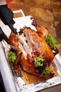 The chef cuts the turkey on a tray in a restaurant