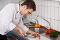 Chef cutting meat on chopping board young at commercial kitchen Stock Images