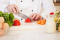 Chef cutting a tomato hands of Royalty Free Stock Photography