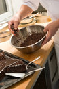 Chef decorating chocolate cake with icing sugar dark brown Royalty Free Stock Photos