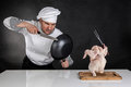Chef fighting with knife and pan raw chicken attack Royalty Free Stock Photo