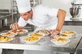 Chef garnishing dishes at counter young male commercial kitchen Royalty Free Stock Image