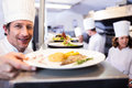 Chef handing dinner plates through order station Royalty Free Stock Photo