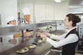 Chef handing food dish to waitress at order station Royalty Free Stock Photo
