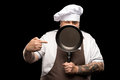 Chef in hat and apron winking and pointing on frying pan isolated on black Royalty Free Stock Photo