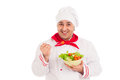 Chef holding dish with salad and fresh vegetables wearing red and white uniform over background Royalty Free Stock Photos