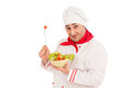 Chef holding dish with salad and fresh vegetables wearing red white uniform over white background Stock Photo