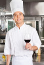 Chef holding glass of red wine portrait handsome in commercial kitchen Royalty Free Stock Image