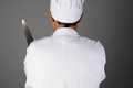 Chef holding knife closeup of a a man is seen from behind and is unrecognizable horizontal format on a light to dark gray Royalty Free Stock Photos
