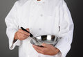 Chef holding mixing bowl and whisk a stainless steel a Stock Image